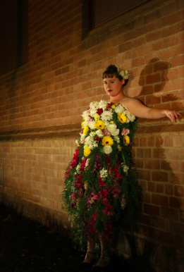 A lady with a dress made out of flowers and vines