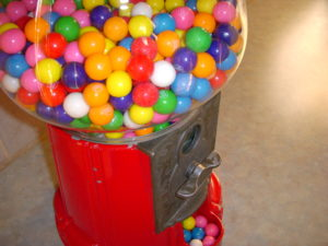 A photograph of a vintage gumball machine